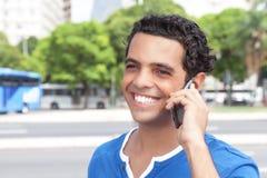 有手机的笑的拉丁人在城市 库存照片