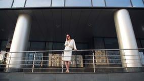 有手机的美丽的典雅的深色的女实业家谈话,微笑和笑在摩天大楼大厦前面的 股票视频