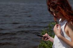 有手机的美丽的妇女在河沿 库存照片