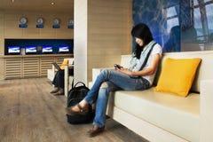 有手机的美丽的旅客在机场。 库存图片