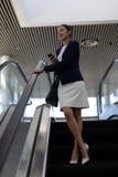 有手机的美丽的mixed-race女实业家使用自动扶梯在现代办公室 库存图片