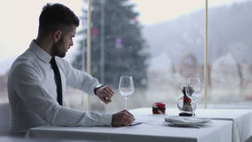 有手机的英俊的人在餐馆 免版税库存图片