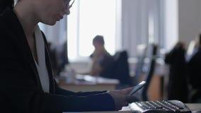 有手机的被用尽的女实业家在办公室特写镜头的一个工作场所后坐 股票录像