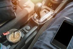有手机的里面汽车在司机用咖啡和照相机请求 库存图片