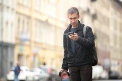 有手机的年轻旅客在街道 库存图片