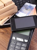 有手机的付款终端有NFC技术、货币欧元,膝上型计算机和被包裹的箱子的在木板台 库存图片