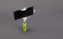 有手机的Selfie棍子在灰色背景 库存图片