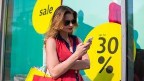 有手机购物的Beautifull妇女在一个室外购物中心。 免版税图库摄影