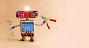 有手板钳和钳子的电工机器人 有一个辉光灯的未来派玩具机器人杂物工 复制空间 免版税库存图片