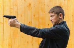 有手枪的少年 库存照片