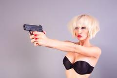 有手枪的白肤金发的女孩 免版税图库摄影