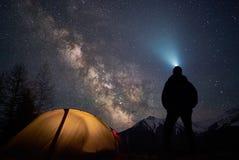 有手电的人游人在他的阵营帐篷附近充分站立在晚上在天空下星 库存图片
