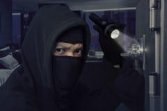 有手电的夜贼打开银行地下室 图库摄影