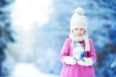 有手电的小女孩和蜡烛在户外冬日 库存照片