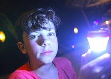 有手电的男孩在夜 免版税库存照片