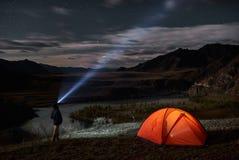 有手电的男性游人在他的阵营帐篷附近在晚上 免版税图库摄影