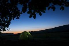 有手电的绿色迁徙的帐篷里面在黑暗的夜空和橡木叶子下 图库摄影