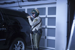 有手电调查的汽车的警察在车库 库存照片