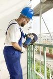 有手研磨机的一名建筑工人切开在建造场所的钢标尺 免版税图库摄影