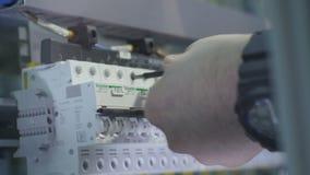 有手表的特写镜头手扭转螺丝在大交换机 股票录像