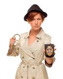 有手铐的恼怒的女性在军用防水短大衣的探员和徽章 免版税库存照片