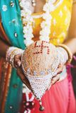 有手镯的印地安新娘在她的拿着椰子shagun的腕子nariyal为印地安婚姻仪式 库存照片