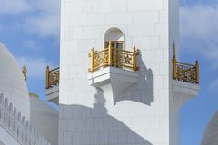有扎耶德与蓝天的Grand Mosque回教族长装饰的金黄路轨的特写镜头大理石走廊在阿布扎比,阿拉伯联合酋长国的早晨 免版税库存照片