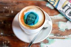 有打印的面孔的咖啡杯在泡沫 免版税库存图片