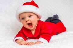 有打呵欠圣诞老人的服装的逗人喜爱的新出生的婴孩 库存照片
