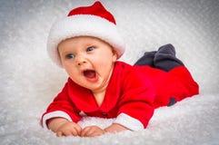有打呵欠圣诞老人的服装的逗人喜爱的新出生的婴孩 免版税库存照片