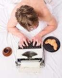有打字机和咖啡位置床的人 创作人繁忙被弄乱的头发写章节最后期限以后的顶视图 人 免版税库存图片