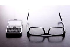 有打字机键盘的键盘和对的智能手机镜片 免版税库存照片