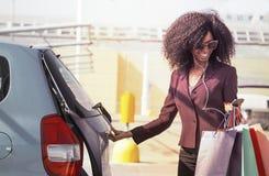 有打开汽车和发短信在手机的购物袋的愉快的非洲妇女 图库摄影
