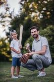 有打棒球的儿子的爸爸 库存图片