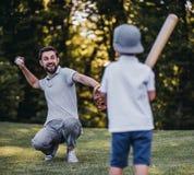 有打棒球的儿子的爸爸 库存照片