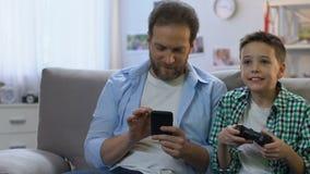 有打电子游戏,在智能手机的父亲卷动的控制杆的年轻男孩 股票视频