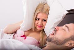 有打鼾在睡眠的丈夫的妻子 免版税库存图片