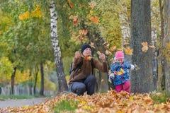 有扔黄色秋叶的小女儿的愉快的父亲在公园户外 库存照片
