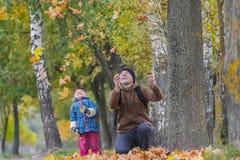 有扔黄色秋叶的笑的女儿的微笑的父亲在公园户外 图库摄影