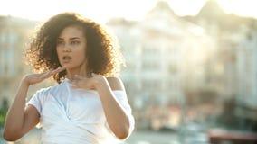 有执行在都市背景的卷发的一名年轻可爱的微笑的妇女跳舞 股票视频