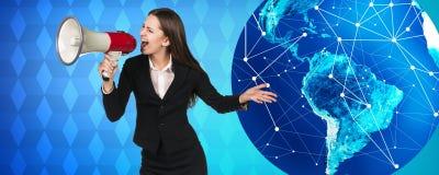 有扩音机的妇女在大地球附近站立 免版税库存照片