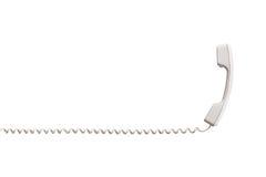 有扭转的导线的白色手机,水平地被舒展 库存照片