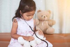 有扮演医生的听诊器的逗人喜爱的亚裔小孩女孩 库存图片