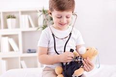 有扮演医生的玩具熊的孩子 免版税图库摄影