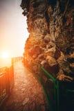 有扶手栏杆的道路在日落的高山 库存图片