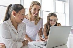 有技术片剂和手提电脑的孩子在背景的教室老师 免版税图库摄影