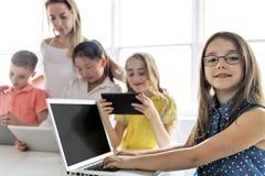 有技术片剂和手提电脑的孩子在背景的教室老师 免版税库存图片