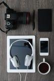 有技术设备片剂、照相机和耳机的办公桌 免版税库存图片