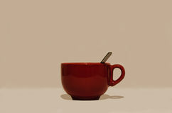 有把柄和匙子的大光滑的红色圆的杯子 免版税库存图片