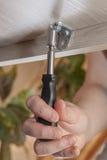 有把柄插口六角扳手坚果锭床工人的手拉紧,特写镜头 图库摄影